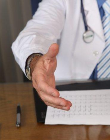 Dobry lekarz reumatolog wyciagający pomocną dłoń.